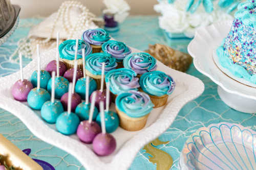blue and purple cupcakes and cake pops on a party table